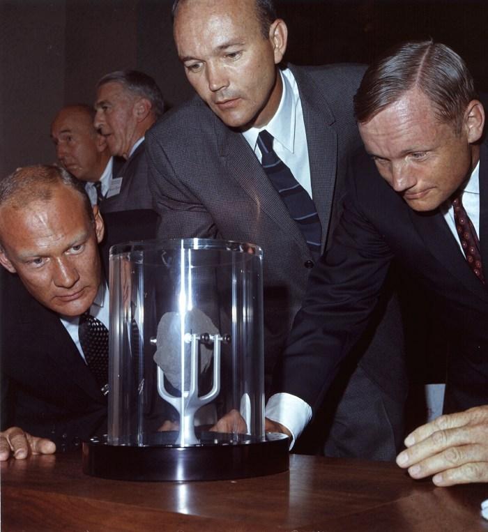 Aldrin, Collins i Armstrong przyglądają się próbce skały, którą przywieźli z Księżyca
